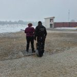 Kuvassa ampuja ja vamentaja lumisateessa skeet radalla